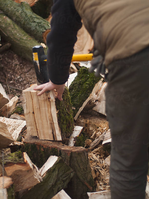 A man splitting logs by Neil Warburton for Stocksy United