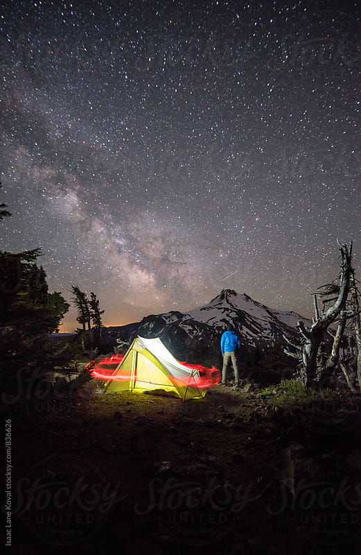 Man standing watch in front of Mt Jefferson with starry night sky by Isaac Lane Koval for Stocksy United