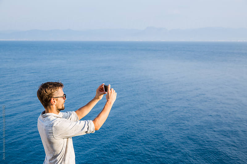 Handsome young man wearing sunglasses taking a photo of the horizon at sea by Jovo Jovanovic for Stocksy United