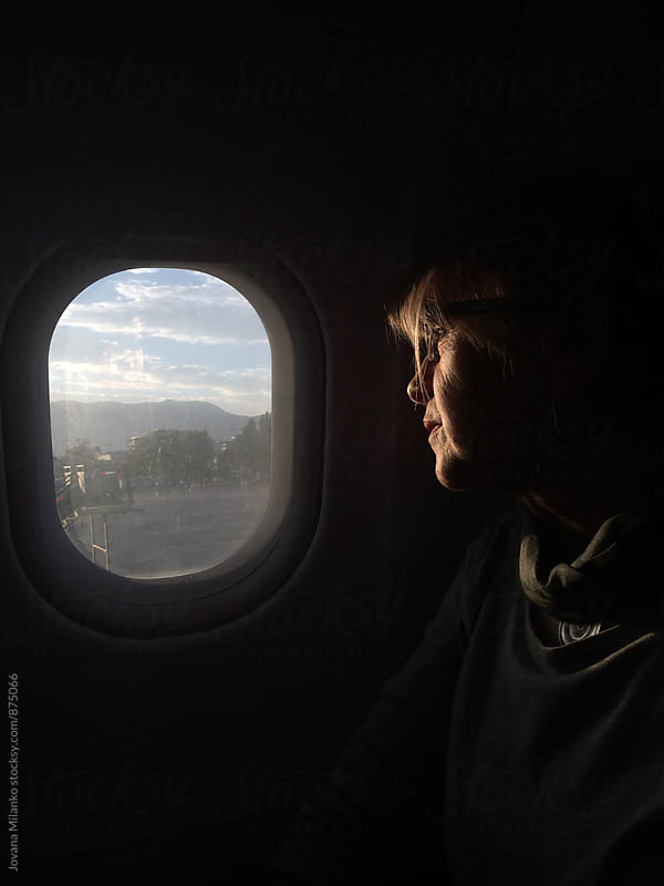 Senior woman looking trough the airplane window on departure by Jovana Milanko for Stocksy United