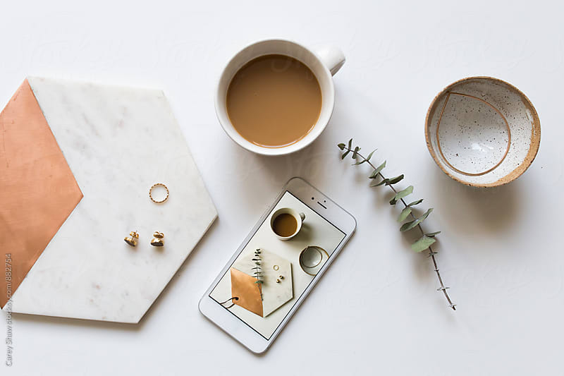 Clean desktop with coffee, phone, and jewelry by Carey Shaw for Stocksy United