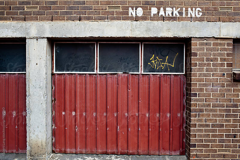 No parking vandalism on suburban brick wall by Robert Lang for Stocksy United