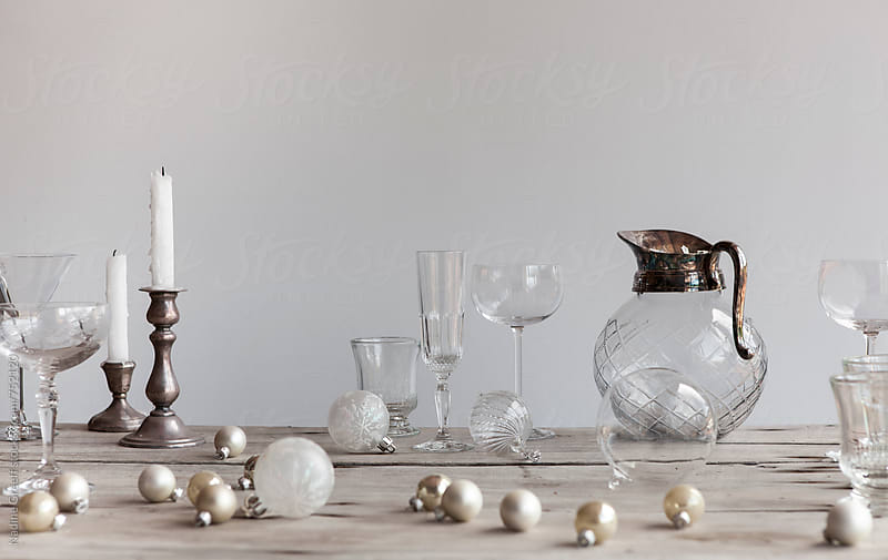 Cocktail and drinks glasses with scattered  christmas decorations on wooden table by Nadine Greeff for Stocksy United