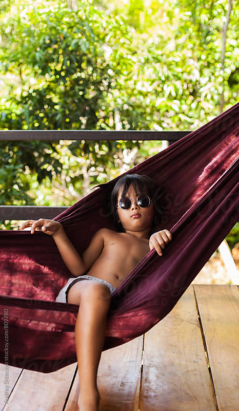 Portrait of cute little kid/boy relaxing in hammock . by Audrey Shtecinjo for Stocksy United