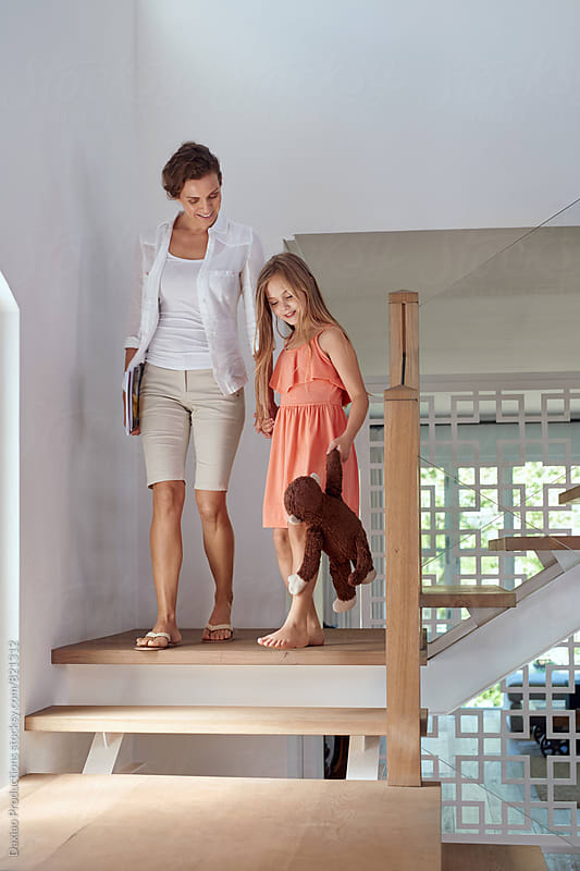 mother and daughter walking down stairs by Daxiao Productions for Stocksy United