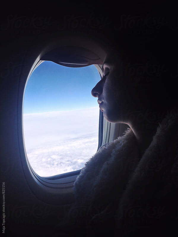 Young woman sleeping in aeroplane by Maja Topcagic for Stocksy United
