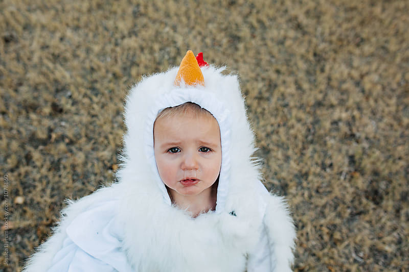Sad toddler boy dressed up in a chicken suit for Halloween with snot running down his nose. by Jessica Byrum for Stocksy United