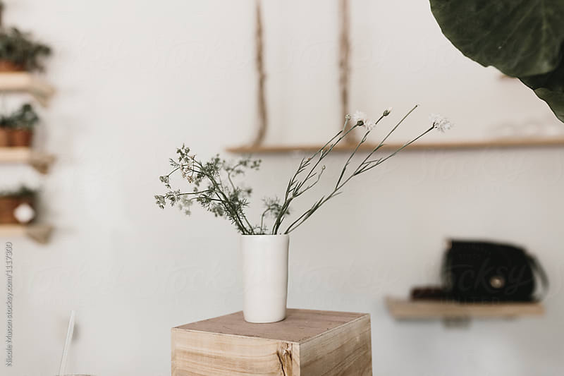white vase of stems and small flowers
