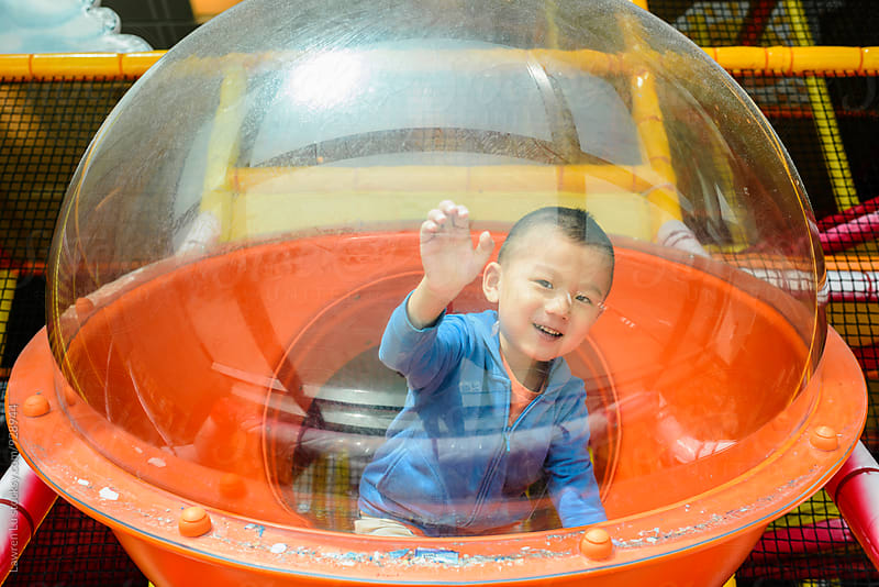 cheerful little boy inside transparent spherical attraction by Lawren Lu for Stocksy United