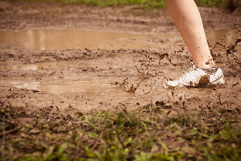 Close up of a female runner running through the mud. by Mosuno for Stocksy United