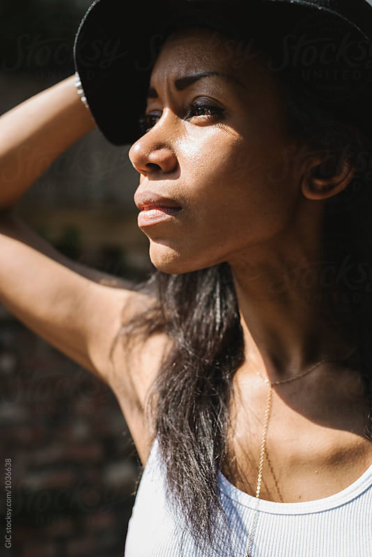 Beautiful black woman portrait with hat by Simone Becchetti for Stocksy United