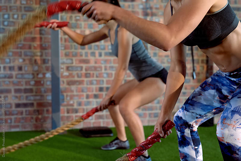 women doing exercises with ropes at a gym by Daxiao Productions for Stocksy United