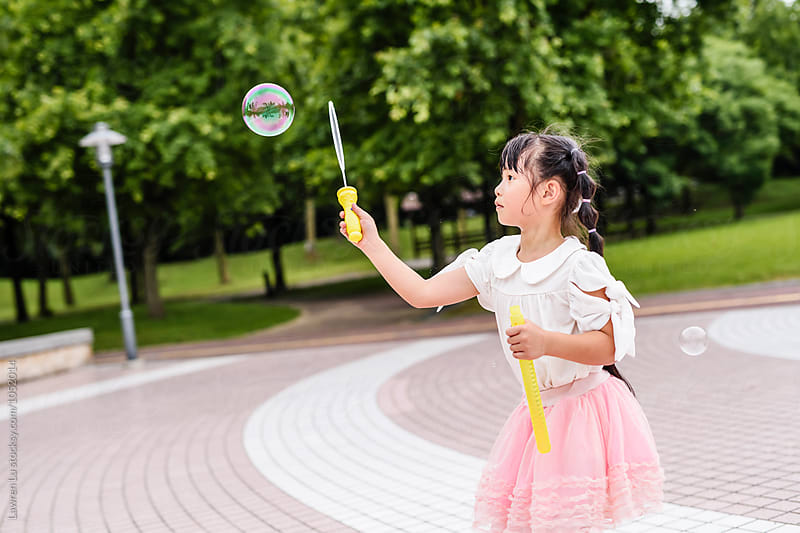 side view of asian girl playing with soap bubbles by Lawren Lu for Stocksy United