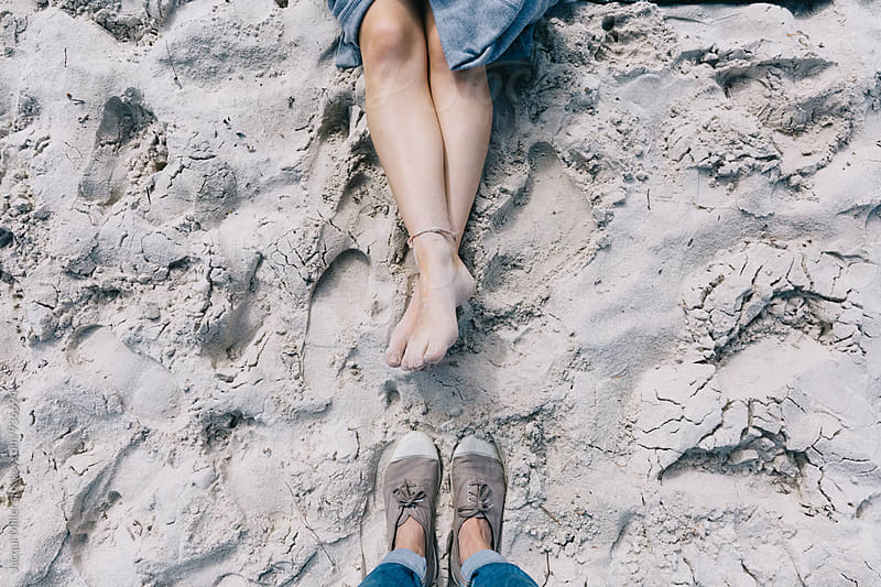 Looking down on feet at the beach by Jacqui Miller for Stocksy United