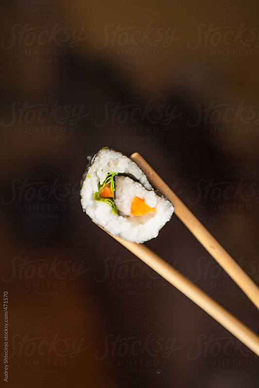 Sushi roll held with chopsticks - close up.  by Audrey Shtecinjo for Stocksy United
