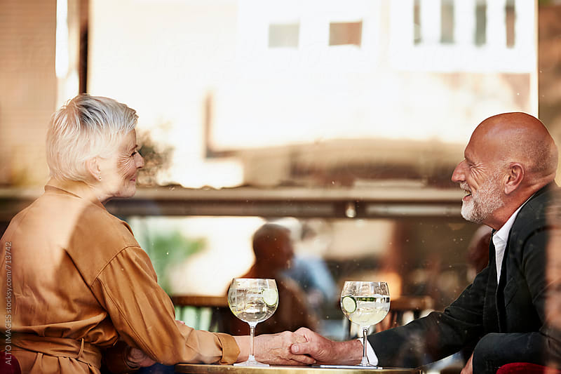 Senior Couple Holding Hands In Restaurant by ALTO IMAGES for Stocksy United