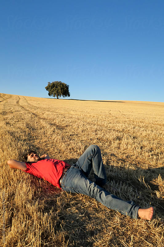 A man resting in a wheat field on summer by Bisual Studio for Stocksy United