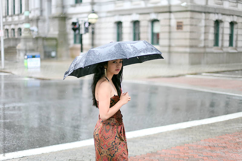 Woman in formal dress standing on a city corner in the rain by Jennifer Brister for Stocksy United