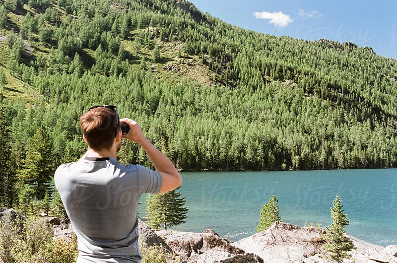 Man looking through binoculars by Milles Studio for Stocksy United