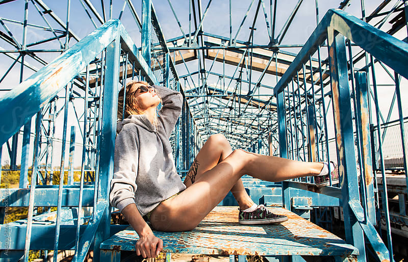 Sensual young woman in urban outfit enjoyiing sun on metal construcion. by Audrey Shtecinjo for Stocksy United