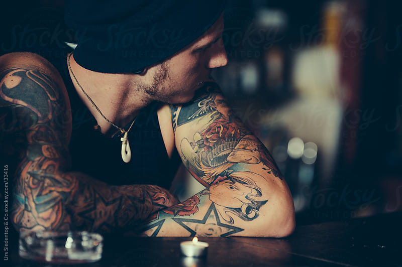Man with mexican tattoo in pub by Urs Siedentop & Co for Stocksy United