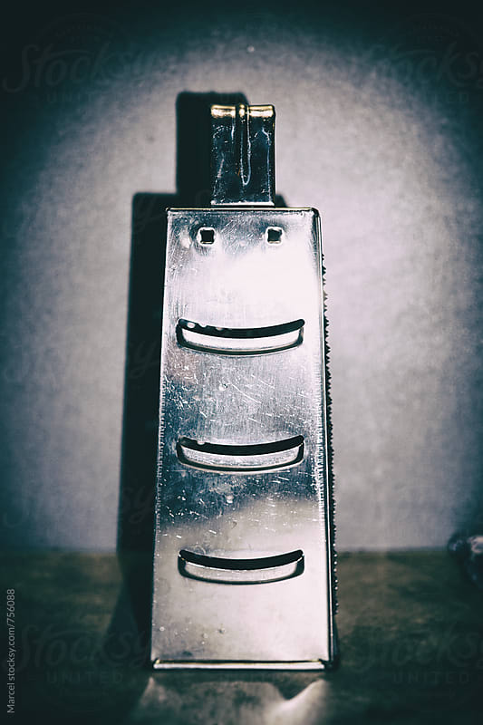 Smiling face on a metal grater by Marcel for Stocksy United
