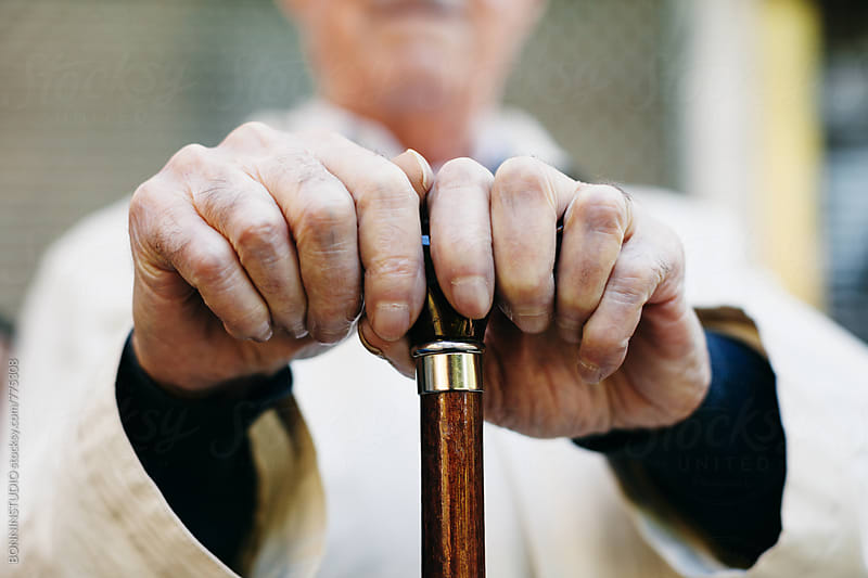 Closeup of an elderly man holding a stick sitting outside. by BONNINSTUDIO for Stocksy United