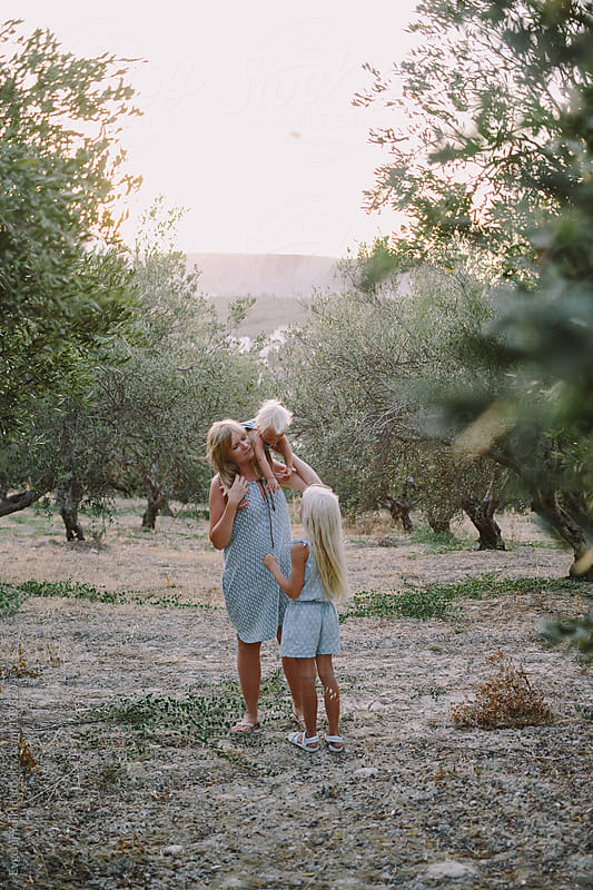 Woman with her daughters in olive grove by Evgenij Yulkin for Stocksy United