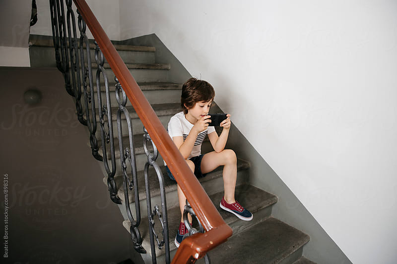 Boy playing a game on a cellphone while sitting on stairs by Beatrix Boros for Stocksy United