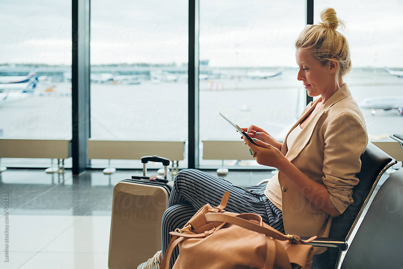 Woman With a Tablet at  an Airport Departure Lounge by Lumina for Stocksy United