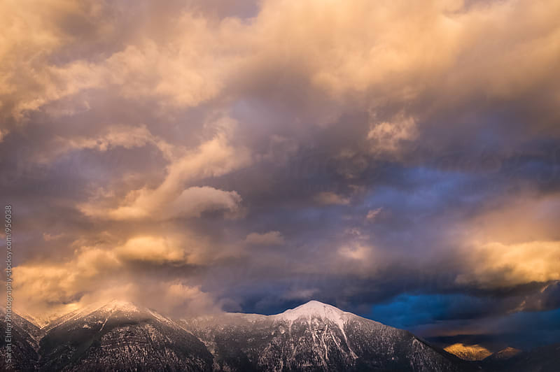 A scenic view of a beautiful pink sunset and clouds over the mountains by Sarah Ehlen Photography for Stocksy United