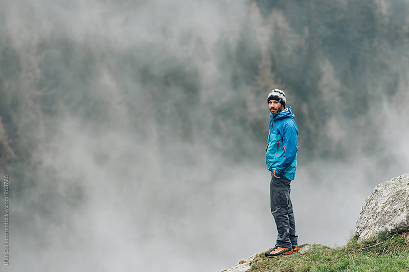 Male hiker overlooking beautiful foggy forest views by Jordi Rulló for Stocksy United