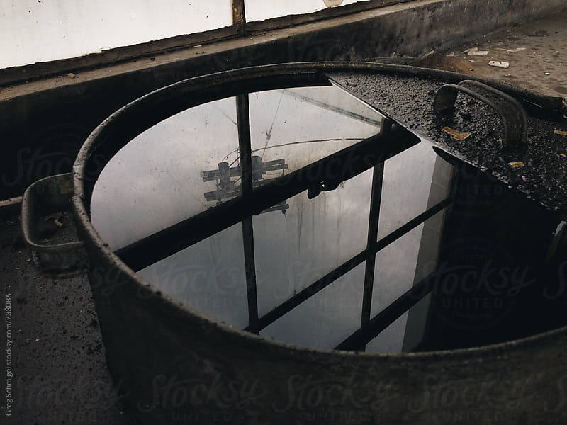 Reflection of light in an old grungy oil barrel in an abandoned garage by Greg Schmigel for Stocksy United