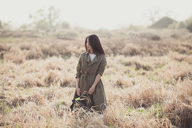 Asian girl with a backpack in the wilted fields by Irina Efremova for Stocksy United
