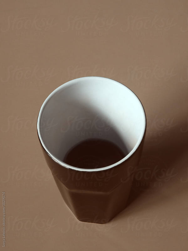 brown coffee cup on brown background by Sonja Lekovic for Stocksy United