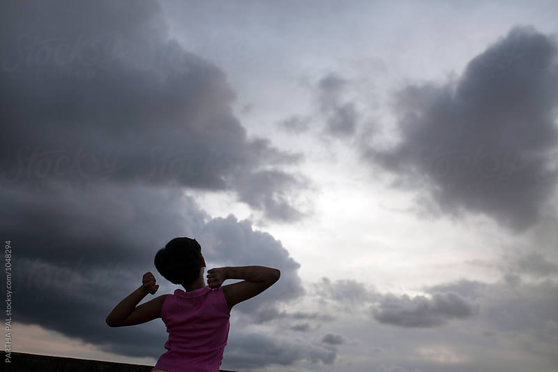 Teenage girl stretching arms with monsoon sky at backdrop by PARTHA PAL for Stocksy United