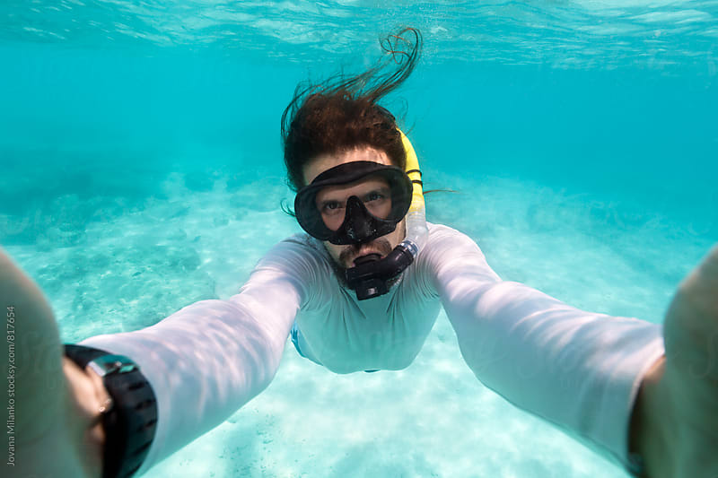Young man taking selfie while snorkeling in turqoise tropical water of Phi Phi Island in Thailand by Jovana Milanko for Stocksy United