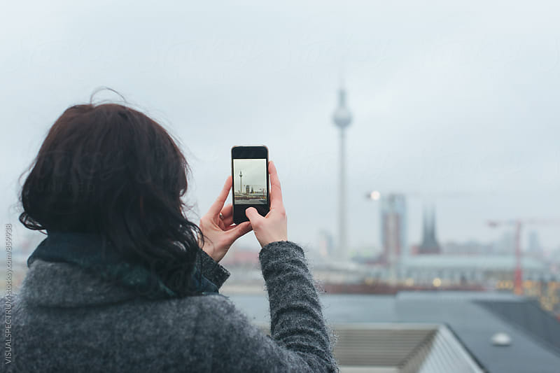 Woman Taking Smartphone Photo of Berlin's TV Tower on Rainy Winter Day by Julien L. Balmer for Stocksy United