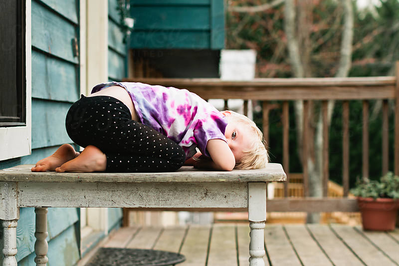 young girl resting on table by Jess Lewis for Stocksy United