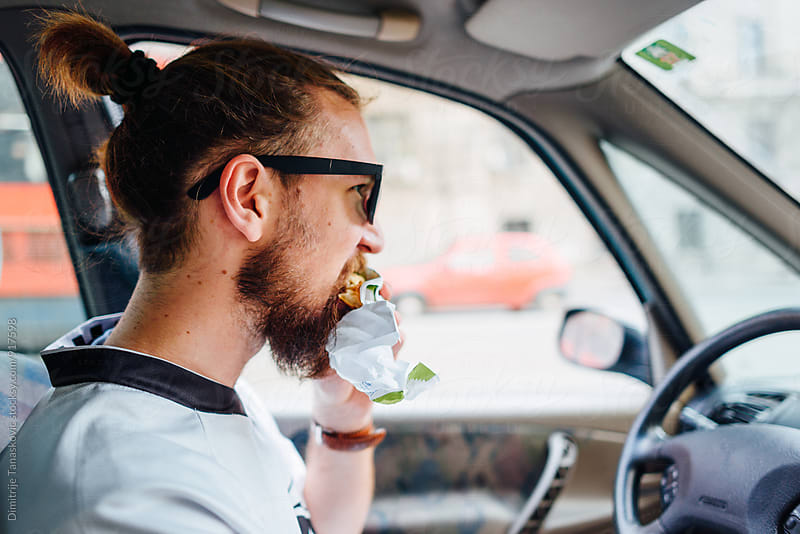 Man eating in the car by Dimitrije Tanaskovic for Stocksy United