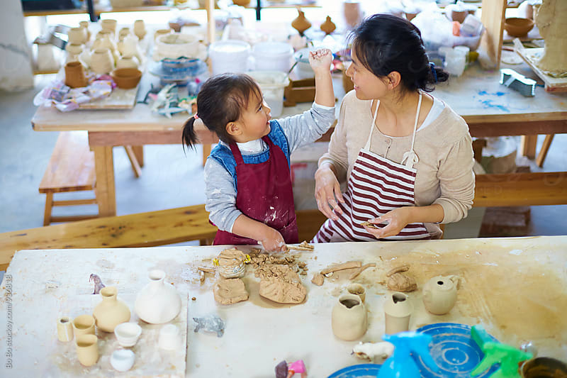 little asian girl with her mother in the pottery studio by Bo Bo for Stocksy United