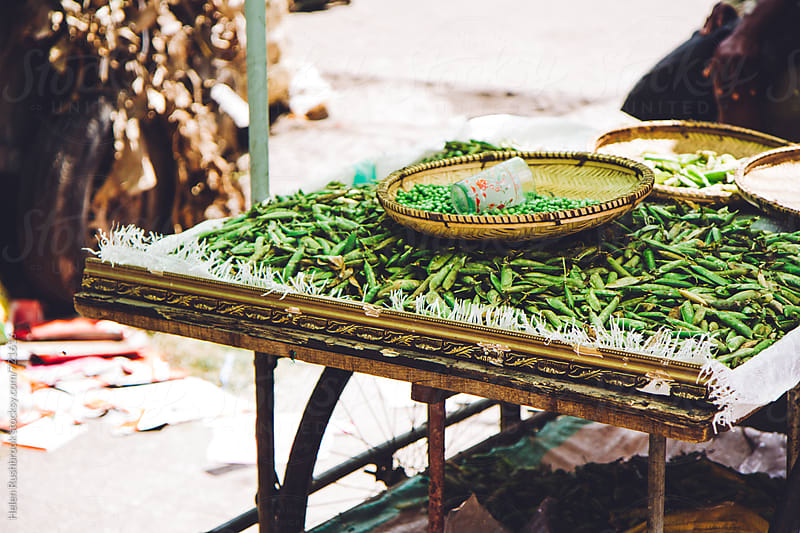 Fresh peas on an African market stall by Helen Rushbrook for Stocksy United
