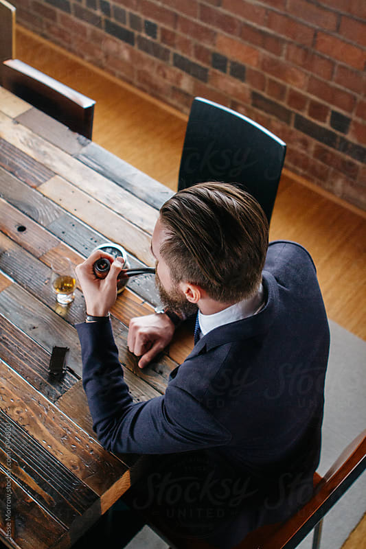 Young man sits at table smoking pipe with glass of whiskey by Jesse Morrow for Stocksy United