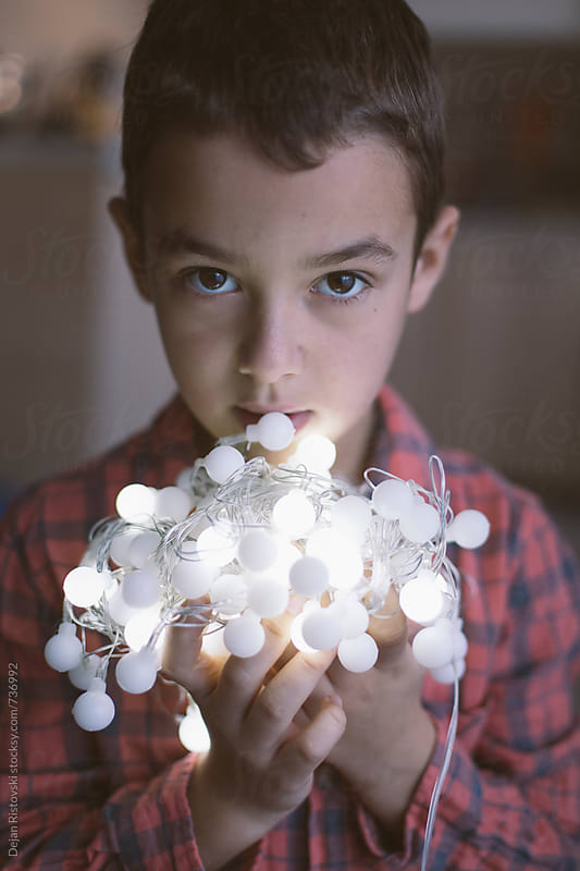 Boy holding lights by Dejan Ristovski for Stocksy United