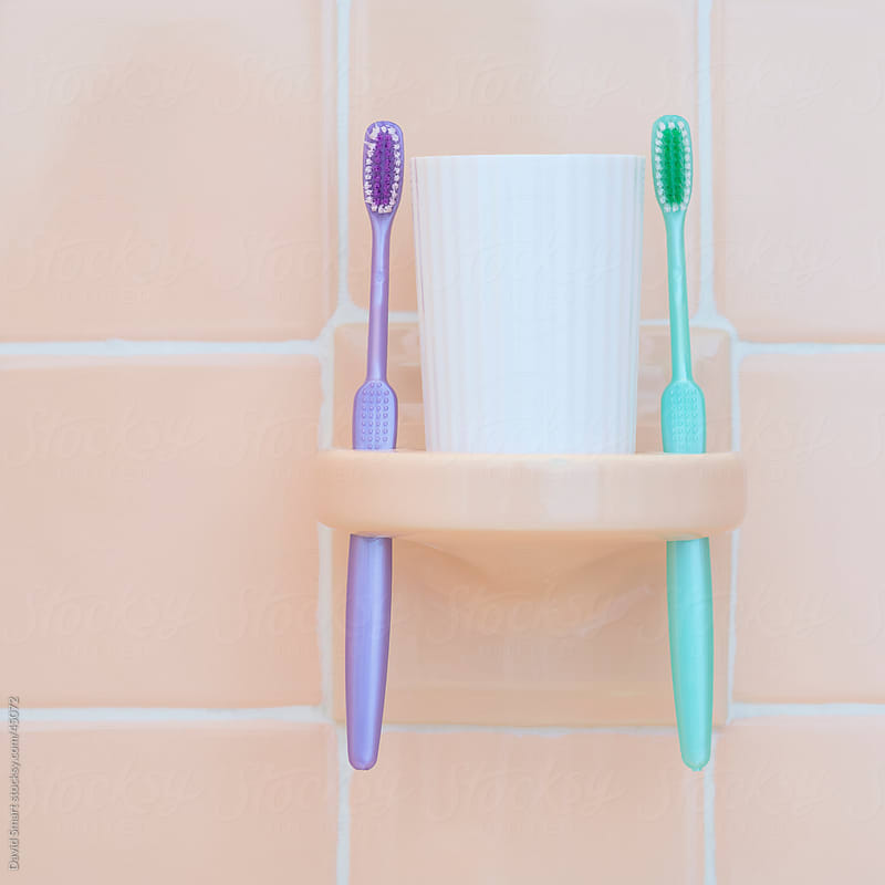 Toothbrushes in a porcelain tile holder with a white cup by David Smart for Stocksy United