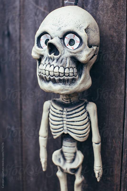 Cute, big eyed skeleton decoration on a fence for Halloween by Carolyn Lagattuta for Stocksy United