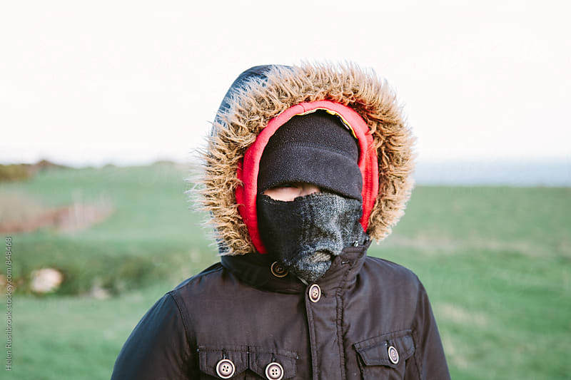 Teenage boy wrapped up against the weather by Helen Rushbrook for Stocksy United