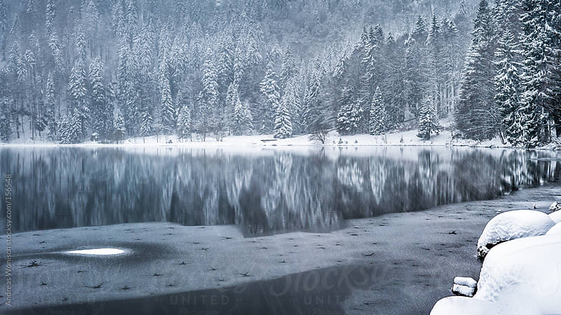 Partially frozen lake during Snow Fall by Andreas Wonisch for Stocksy United