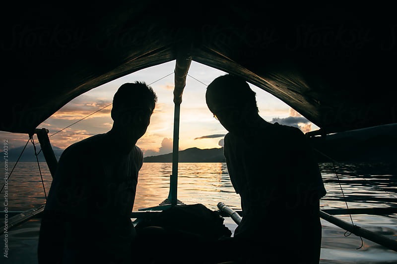 Two men on a boat at sunset, silhouettes. by Alejandro Moreno de Carlos for Stocksy United