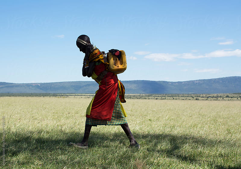 Maasai woman carrying water. Kenya. Africa. by Hugh Sitton for Stocksy United
